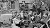 Noni Wright interviewing RNZAF aircrew for a radio broadcast to New Zealand in 1943. Robert Dall is seated an wearing a forage cap.