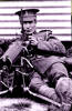 Portrait, full length lying down with machine gun, foot extended and hobnails showing, patch on sleeve - No known copyright restrictions