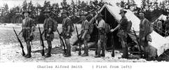 Group, WW1, 7 soldiers standing in a line all wearing shorts, sleeves rolled up, rifles, knap sacks, daggers and other equipment, snow on the ground, line of pine trees and two tents in background. other men in background. - No known copyright restrictions