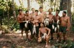 Members of 10 Pl after fishing trip to Perak River with P.E. Left to right: Blackie Graham, D. Naera, B. Brown,  A. McCutcheon, Kay Merito, possibly R. G. Walley, E. J. G. Ormsby, kneeling unidentified. Image taken during Malayan Emergency 1959-1960. © Peter Gallacher.