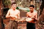 Pte Brian Hills & Dave Naera of 10 Pl with the pick of the catch (a SEBARAU) a freshwater species of Malaysia. Image taken during Malayan Emergency 1959-1960. © Peter Gallacher.
